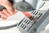 Man dialling out on a telephone — Stock Photo