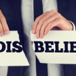 Man holding torn paper with the words Dis-Belief — Stock Photo #50086473