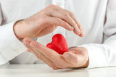 Caring man cupping a red heart in his hands — Stock Photo
