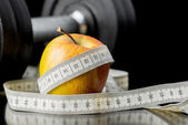 Fresh juicy apple wrapped in a tape measure — Stock Photo