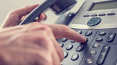 Man dialling out on a landline telephone — Stock Photo