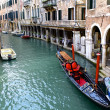 Gondolier And HIs Colorful Gondola On Venetian Canal — Stock Photo