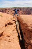 Tourist Straddles Deep Crevice — Stock Photo