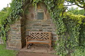 Romantic nook with wood bench and hedge — Stock Photo
