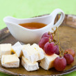 Grapes, cheese and honey on a tray - Stock Photo