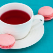 Macaroon and cup of herbal tea — Stock Photo