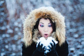 Young woman in a snowy furry hood — Stock Photo