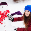 Stock Photo: Pretty girl with snowmin pinewood on winter day