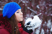 A Girl Wearing Warm Winter Clothes And Hat Blowing Snow In Winte — Stock Photo