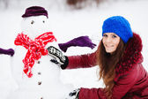 Pretty girl with snowman in pinewood on a winter day — Stock Photo