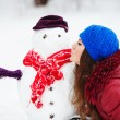 Young Woman Building Snowman In Garden — Stock Photo #39297787