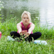 Stock Photo: Beautiful young womdoing stretching exercise on green grass a