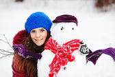 Young Woman Building Snowman In Garden — Stock Photo