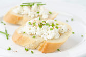 Baguette with cottage cheese and green onions — Stock Photo