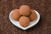 Chocolate truffles on a white plate — Stock Photo