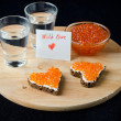 Three sandwich with red caviar in the form of a heart and vodka — Zdjęcie stockowe