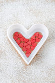 Sugar hearts in white baking dish on a board — Stock Photo