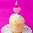 Rum Baba decorated with a lighted candle in the form of heart - Stock Photo