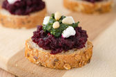 Beet salad with pesto and goat cheese on toasted grain breads — Stock Photo