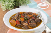 Stew of beef with vegetables and prunes in a plate — Stock Photo