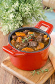 Stew of beef with vegetables and prunes in a red cast iron pan — Stock Photo