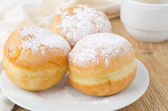 Three sweet donuts sprinkled with powdered sugar — Stock Photo