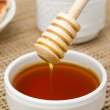 Royalty-Free Stock Photo: Bowl of honey with wooden dipper closeup