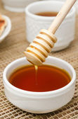 Bowl of honey with wooden dipper closeup — Stock Photo