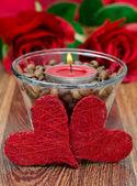 красная свеча в стеклянный стакан с кофе в зернах и два сердца — Стоковое фото