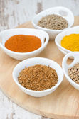 Collection of spices in white bowls (coriander, cumin, paprika) — Stock Photo