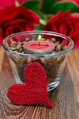 Red candle in a glass cup with coffee beans and decorative heart — Stock Photo