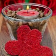 Foto Stock: Red candle in a glass cup with coffee beans and two hearts