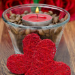Red candle in a glass cup with coffee beans and two hearts — Foto de Stock