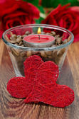 Red candle in a glass cup with coffee beans and two hearts — Stock Photo