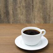 Taza de café con vapor sobre una mesa de madera — Foto de Stock