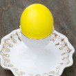 Egg painted in yellow on the stand — Stock Photo