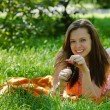Girl is lying on the grass and smiling - Stock Photo