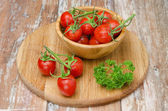 Cherry tomatoes in wooden bowl — Stock Photo
