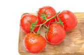 Gren av färska tomater på träplatta isolerad på vit — Stockfoto