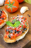 Italian bruschetta with tomato, olives, basil and cheese — Stock Photo
