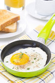 Fried eggs in a frying pan, crisp toast, coffee and orange juice — Stock Photo
