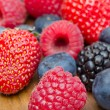 Assorted berries on wooden background - Foto Stock
