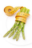 Dietetic food - asparagus wrapped with a measuring tape — Stock Photo