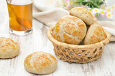 Homemade cottage cheese bread rolls in a basket and a cup of tea — Stock Photo