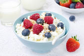 Bowl of cottage cheese with berries, honey and nuts — Stock Photo