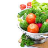 Fresh vegetables and herbs in metal colander, isolated — Stock Photo