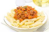 Penne pasta met saus van rundvlees, tomaat en pompoen op een plaat — Stockfoto