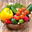 Assorted fresh vegetables and herbs in a wicker basket — Stock Photo