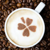 Cup of cappuccino with cinnamon pattern on background of coffee — Stock Photo