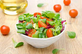 Fresh salad and cherry tomatoes in a bowl, olive oil — Stock Photo